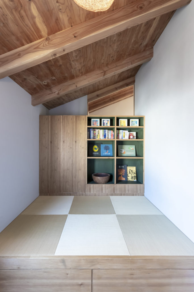 ゲストルームには小上がりを設け、琉球畳を敷いた。クローゼットと棚の裏側は共用部の本棚になっており、壁代わりでもある。