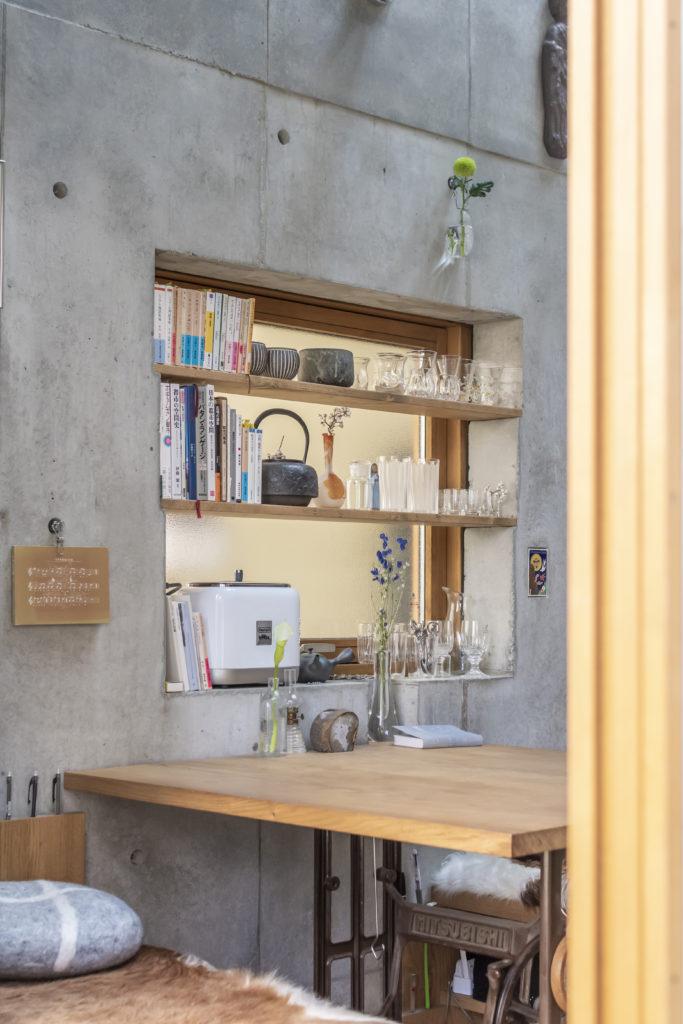道路から室内を見る。窓の部分も収納に活用。棚はコンクリートに付けた凹みに載せているだけ。