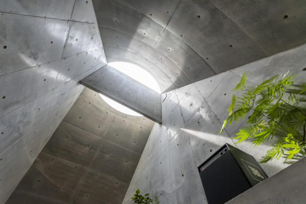 天井を見上げる。トップライトは2つの円弧からできている。ぶら下がっているコンクリートの壁は南からの光を反射させてベッド上の天井を照らす。