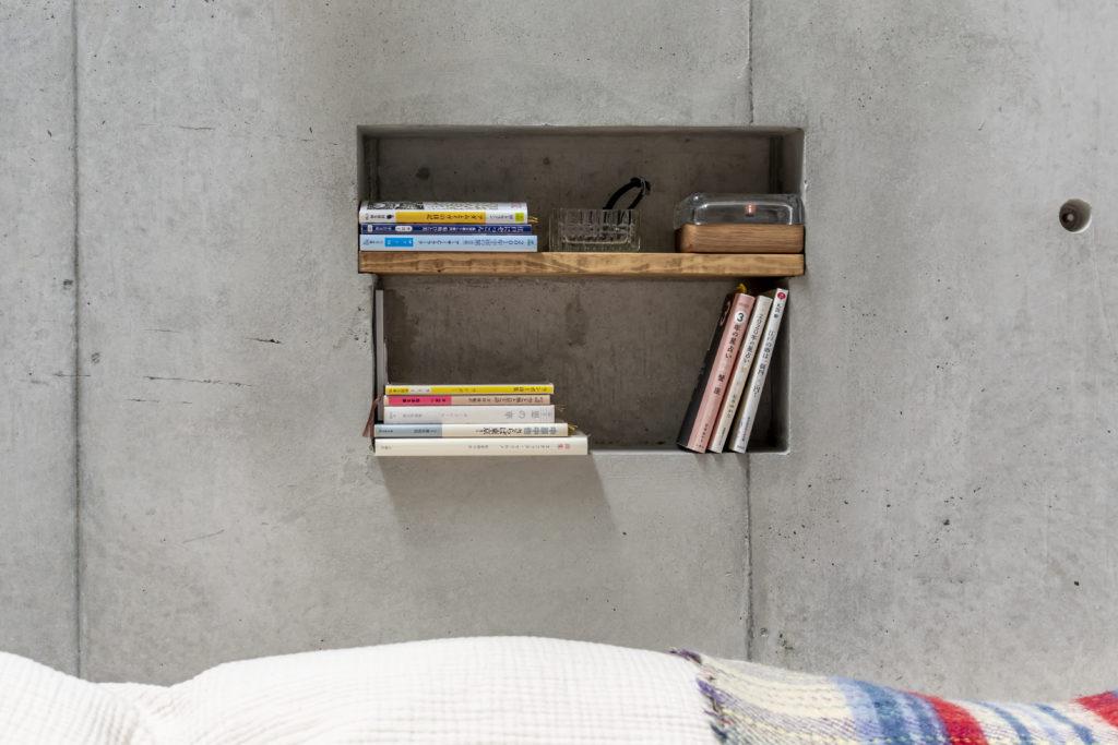 コンクリート壁にいくつかニッチをつくって収納スペースにしている。