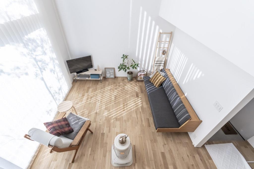 2階からリビングを見下ろす。4mあるブラインドを通して、光が室内に届けられる。