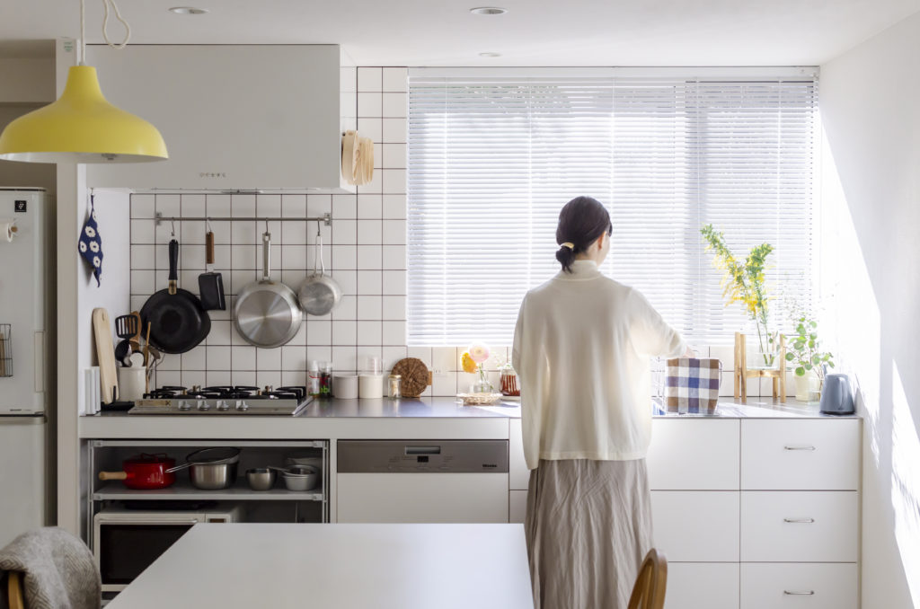 キッチンには窓が欲しかった、という竹内さん。身長に合わせて高さを設定。窓辺には季節の花やグリーンを欠かさない。