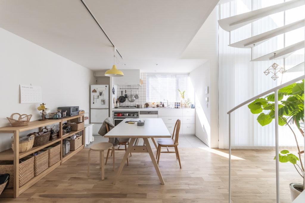 カゴを収納に活用。家具は試行錯誤ののち、現在の配置に。キッチンのみ床を切替えた。