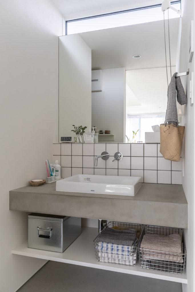 洗面はモルタル仕上げに、キッチンと同じタイルがアクセント。上部にも開口を設けて光を通している。