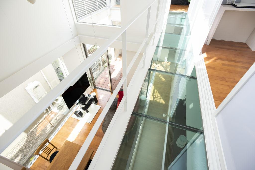 """2階の廊下から1階リビングを見下ろす。""""ガラスのブリッジ""""は、まるで空を渡るような感じからネーミング。トップライトやバルコニーからの光が1階まで届けられる。"""