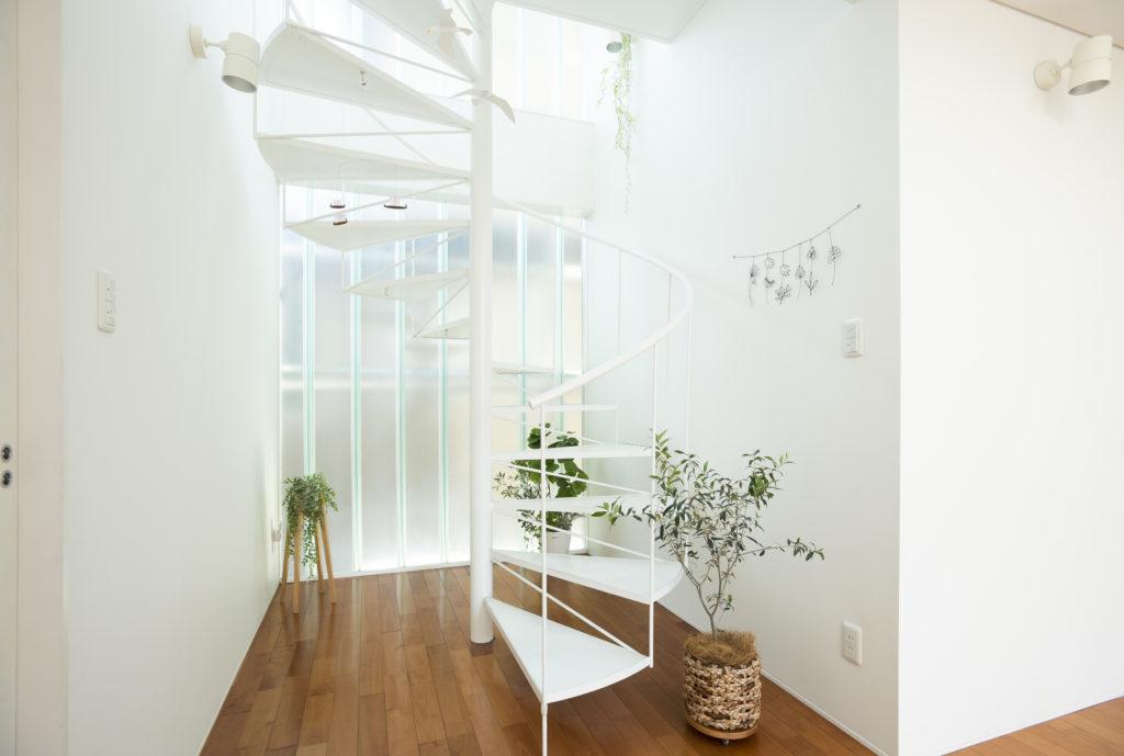 螺旋階段を採用して、階段を抜けのある空間に。開口の代わりにプロフィリットガラスで外からの視線を避けつつ、光を通している。