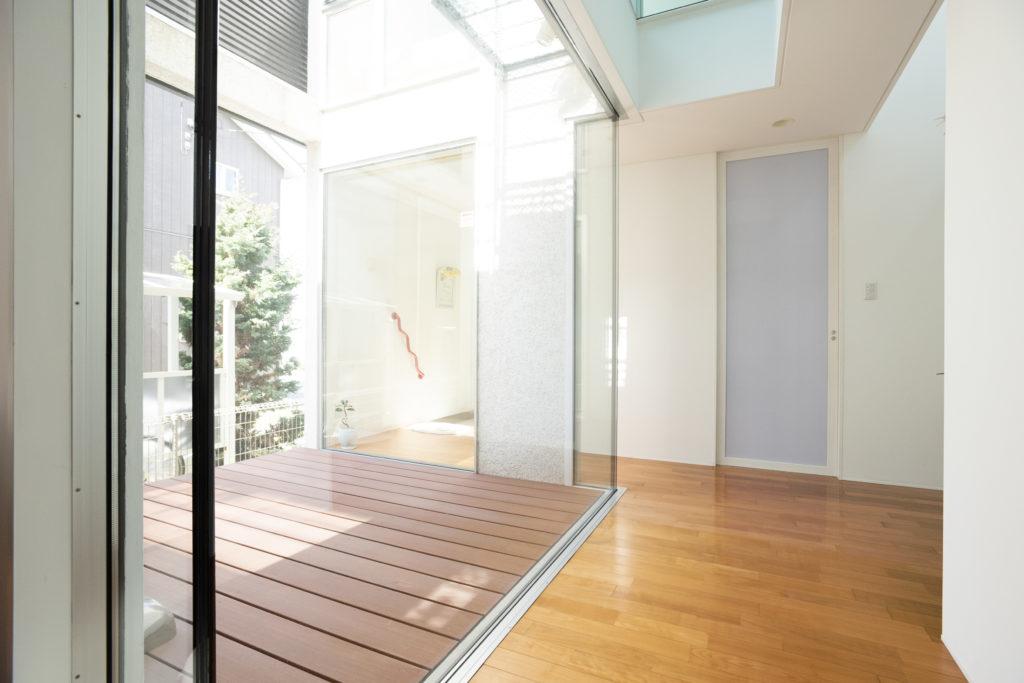 ガラス張りの吹き抜けテラスでは、いずれガーデニングも行う予定。廊下突き当たりの扉の奥は、玄関からもつながっているシューズクローゼット。