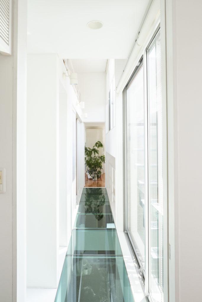 ガラスのブリッジを通って居室に。右手にバルコニーに上がる階段がある。