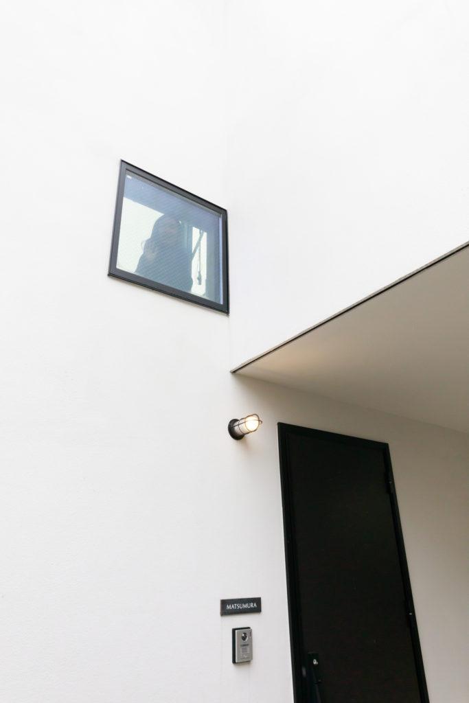 2階の廊下の足元に設けた小窓から、長女が手を振ってくれた。開口が少なめのファサードの中にも遊び心が。