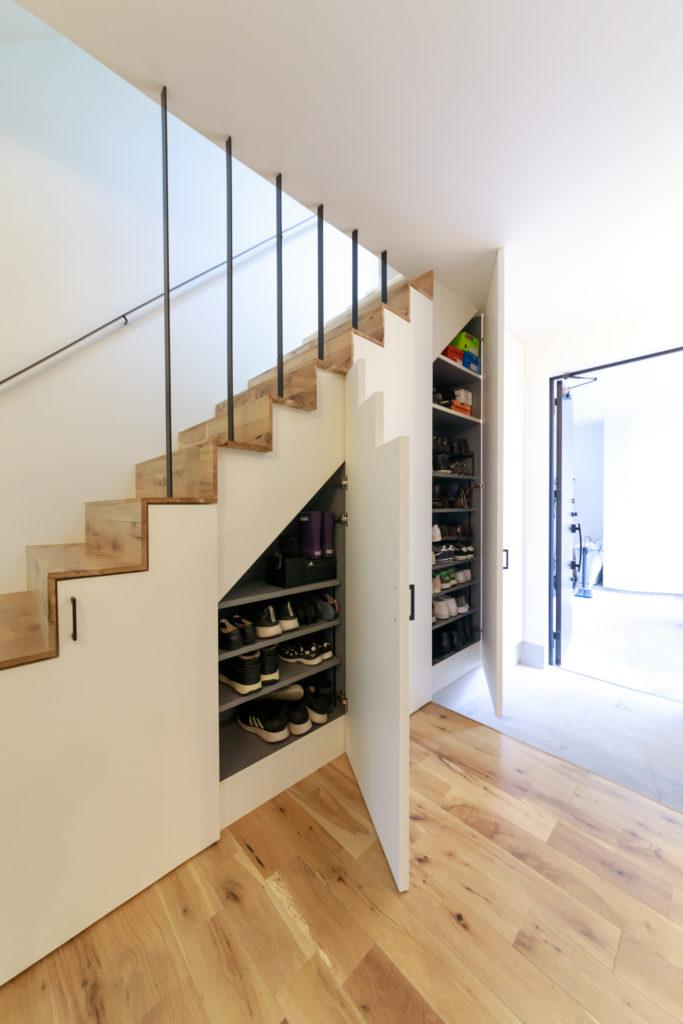 階段下は大容量の靴を収納できるスペースを確保。アパレル関係に勤務するご主人の靴が多いそう。