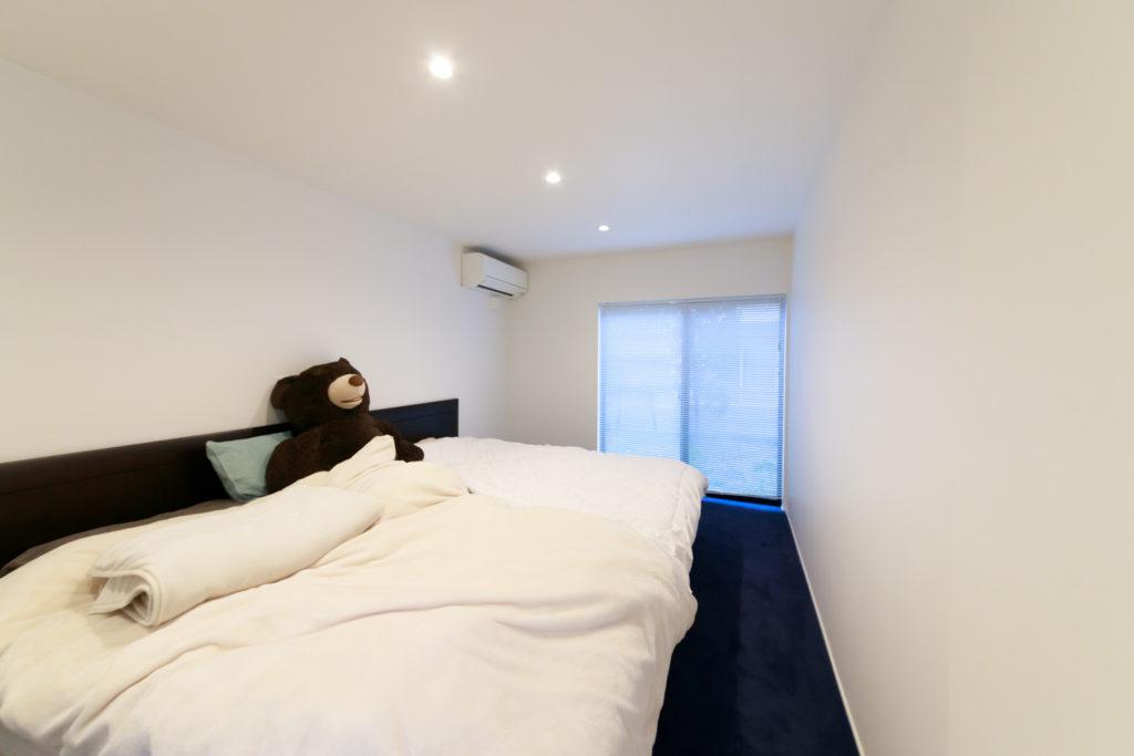 主寝室。部屋の前の廊下から続く濃紺の絨毯が落ち着いた雰囲気。