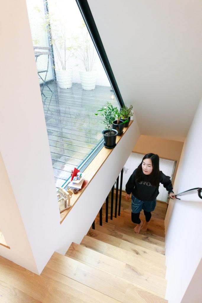 三角形のFIX窓により、光庭から階段へたっぷりの日差しが入り、1階まで光を届けている。