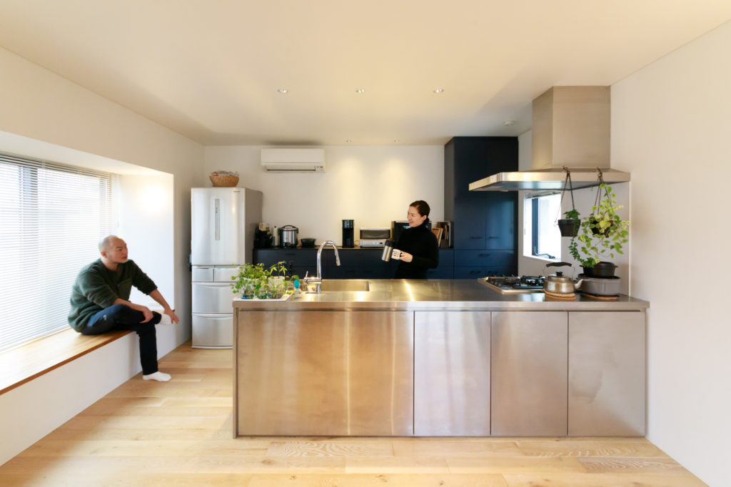 北沢産業でフルオーダーしたオールステンレスのキッチン。左側のベンチは家事の合間に腰掛けたり、物を置いたりするのにも便利とのこと。
