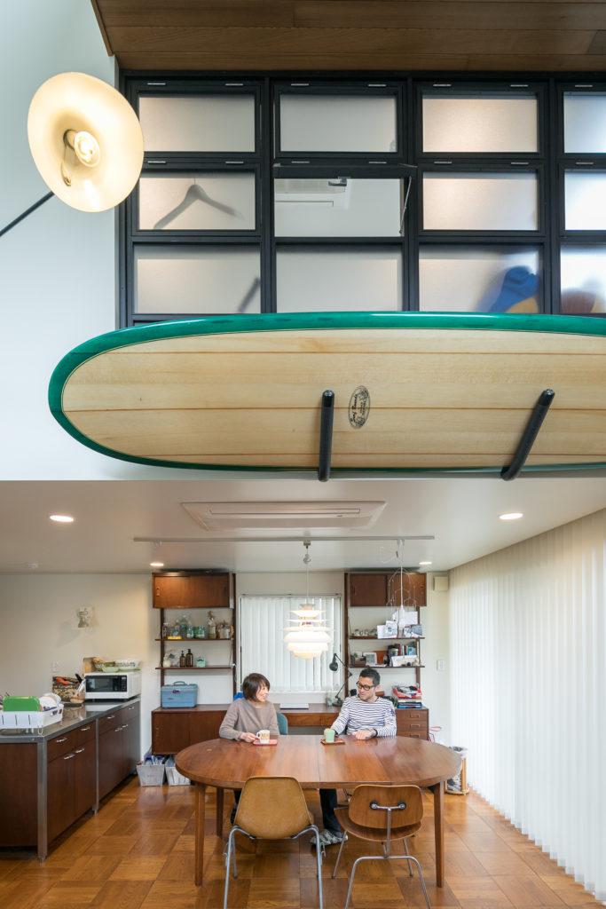 リビング側は吹き抜けになっていて、ダイニング側の2階が個室になっている。吹き抜けに面した窓はリノベーションの際に設置。ダイニングテーブルの後の収納家具はミッドセンチュリーの家具をイメージして製作した。