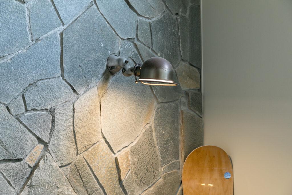 ランダムかつ立体感が感じられるように貼られた天然石がカッコいい。照明はフランスのジェルデライト。