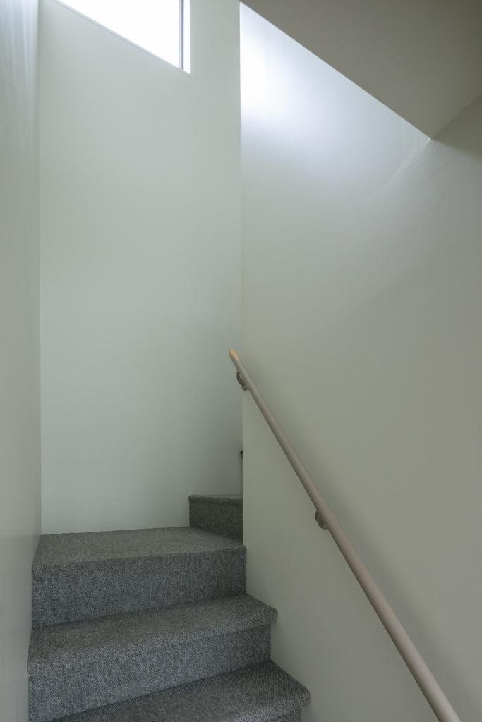 「壁はツヤのある、少しクリームがかった色にしました。このツヤ感がミッドセンチュリーのアメリカの住宅らしさを感じさせてくれます。汚れが落としやすいのも気に入っています」。2階へ上がる階段はカーペット敷に。
