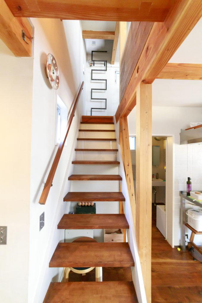 階段の手すり(左側)を変更し、階段右脇にオーク材を重ねて貼り付けたことで、統一感が生まれた。階段上のジグザグのハシゴは、佐賀県の『中島鉄工建設』から取り寄せたもの。ロフトへと続いている。