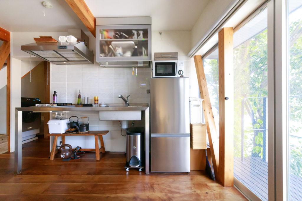 「最初からイメージしていた」という、無駄なものをそぎ落としたフレームキッチン。コンパクトな収納棚に一人用の食器類を収めた。