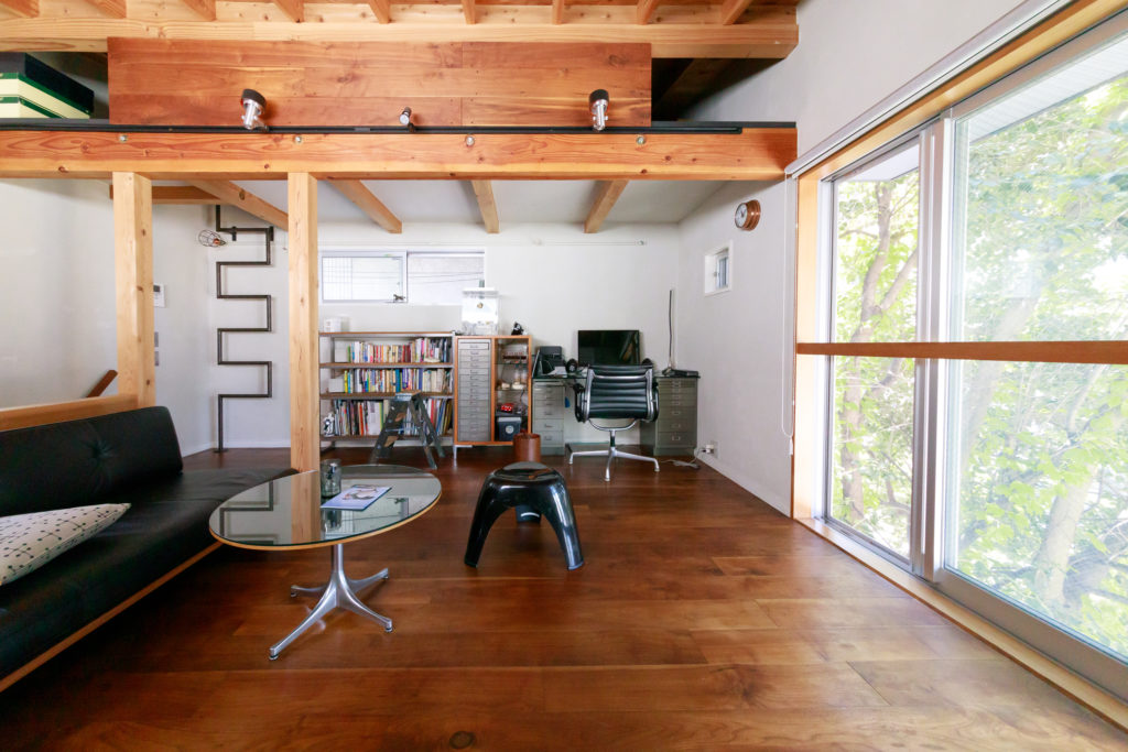 2階リビング。上部は収納として使用しているロフト。「可能な限り大きくした」(志田さん)という窓には木製の枠を付け、さらに十字に木を加えた。「崖側なので、掃除のときの安全のために手すりをつけました」と。木枠が美しいレザーのソファ(左側)は『マスターウォール』。