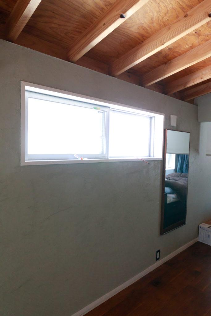 コテでグレーに塗り直した2階の漆喰壁。表面のザワザワ感がいい味を出している。窓からは隣家の反射光を取り入れた。