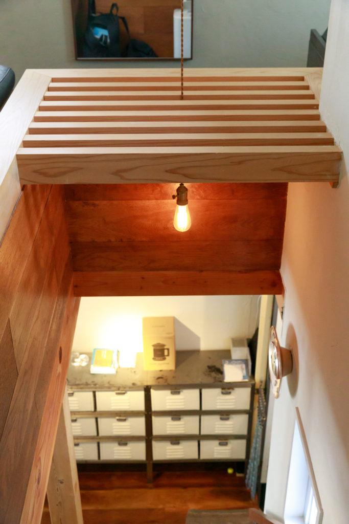 階段の上はスノコ状になっている。スノコの上に伸ばしたアームから隙間を通して照明を吊り下げた。Mさんのアイディア作。のアイディア作。