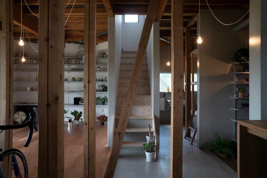 田中邸は築30年ほどの家のリノベーション。階段のあたりを境に1階は土間的な扱いの部分と通常の床の部分とにわかれる。右奥にゲストルーム、その手前に玄関がある。左の木の床の部分がリビング。