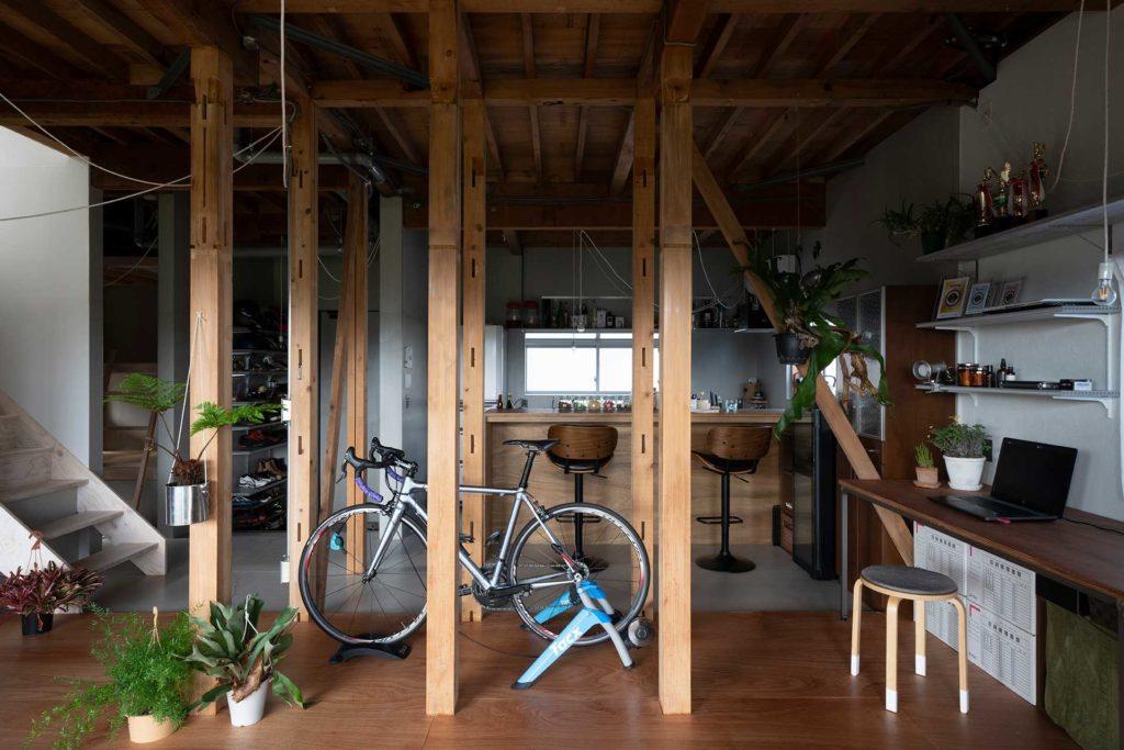 リビングから奥にダイニングキッチンを見る。間にある7本の柱が通常の住宅にはない空気感をつくり出している。ダイニングにはバー用のスツールが置かれている。