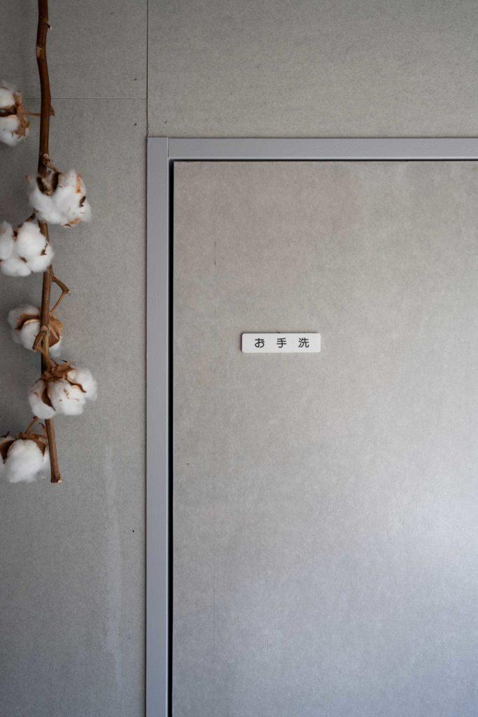 1階の階段下につくられたトイレ。扉に貼られたサインの文字が一昔前のスタイルで空間にマッチしている。