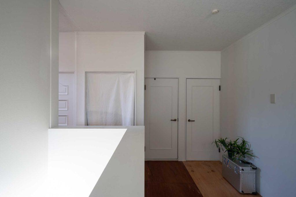 2階の天井と壁は既存のものを白く塗装したのみ。床は張り替えている。左は階段。