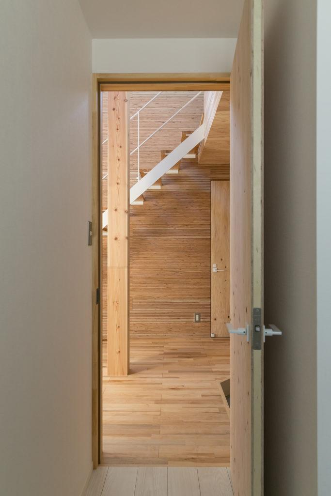 1階の個室から玄関ホールを見る。こちらも、白いクロスのシンプルな個室から温かみのある玄関ホールへの切り替わりで、自然と気持ちも切り替わるようにした。