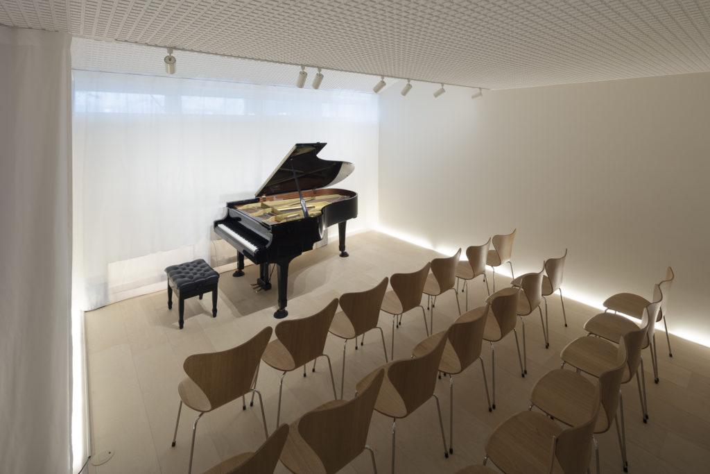 間接光が壁の下部にぐるりとめぐり、また開口のある壁側にはカーテンがかけられているため落ち着いた空気感のあるピアノ室。