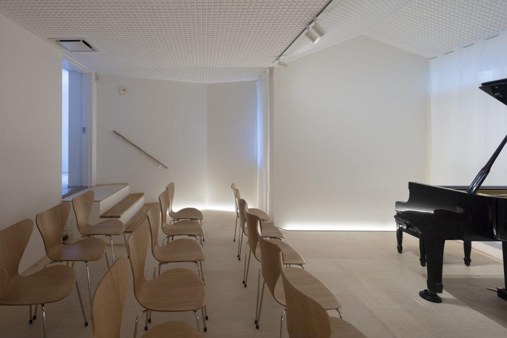 左奥の先にエントランスがありそのレベルからピアノ室は3段下がっている。奥の壁とピアノの上の天井は反響を避けるためにフラットにせず傾斜させている。