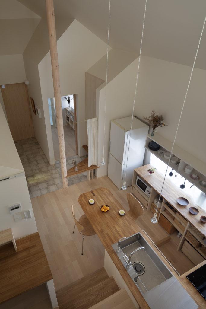 床の仕上げを変え柱を立てることでダイニングと奥のスペースを分節。またキッチンとワークスペースとは階段によってゆるやかに分節されている。ダイニングテーブルは岸本さんにオイルと磨き方を教えてもらい大谷さん自身が塗装した。
