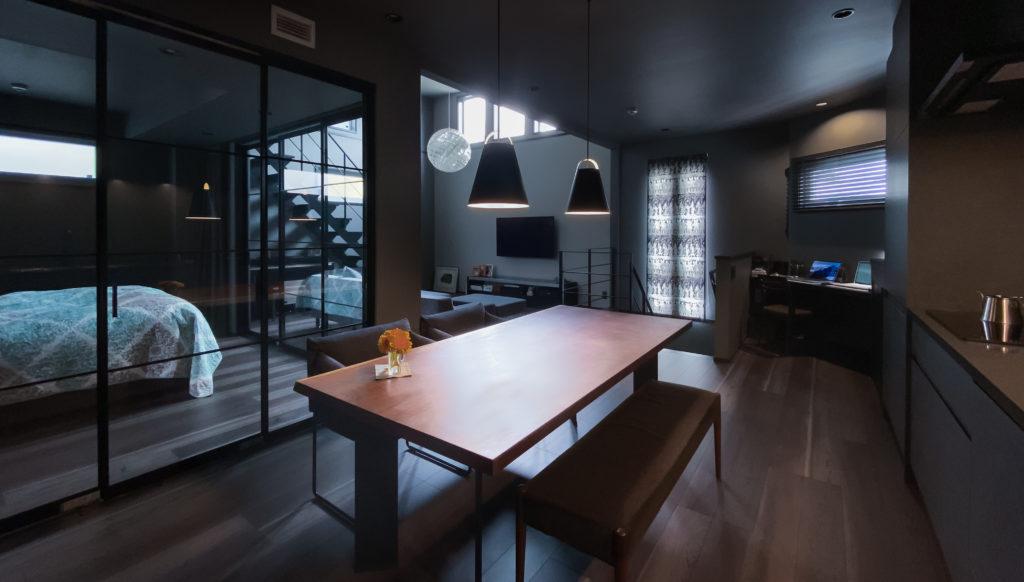 キッチンの奥から二階全体を見渡す。2階はワンルーム的な設計。ダイニング・リビング・寝室を、アイアンのガラス吊り戸とカーテンで仕切っている。