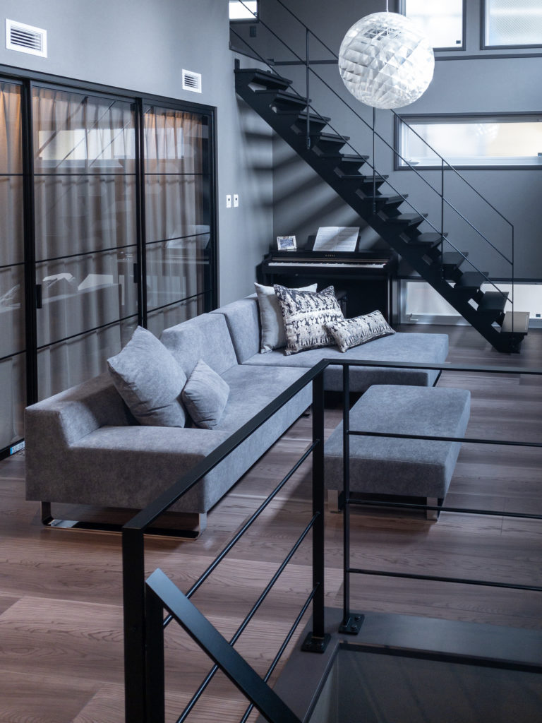 2階やロフトへ上がる階段の手すりもアイアンで統一。北西側にスリット状の明かりとりの窓を設けている。ロフトへの階段下にはピアノを置いた。