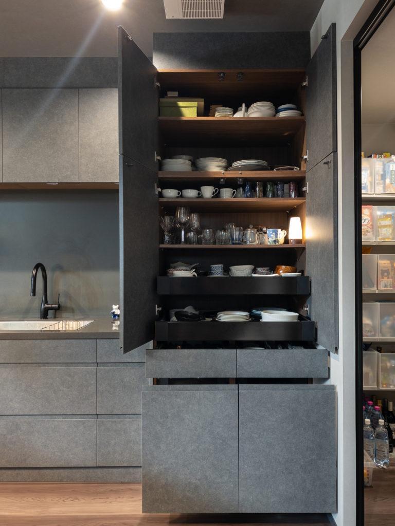 キッチンの収納。扉を開けると広い収納スペースが現れる。引き出しと扉は把手がないタイプを選び、スッキリと見えるように。