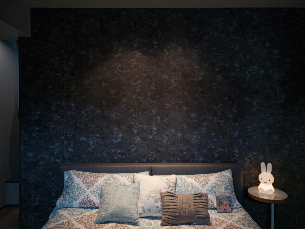 寝室はシックな柄の壁紙を選んだ。ダウンライトを仕込んだ壁の向こうはウォークインクロゼットになっている。