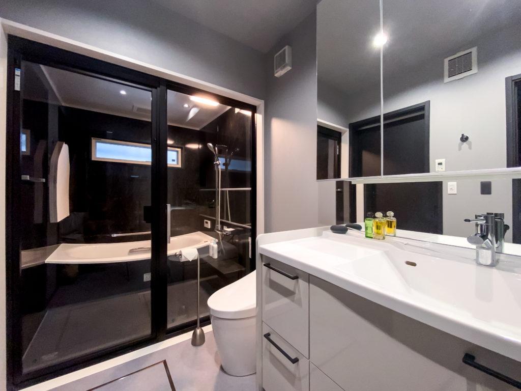 1階のバスルームは、洗面、トイレにランドリーコーナーを合わせて水回りを一箇所に。ガラス張りにして広さを演出。