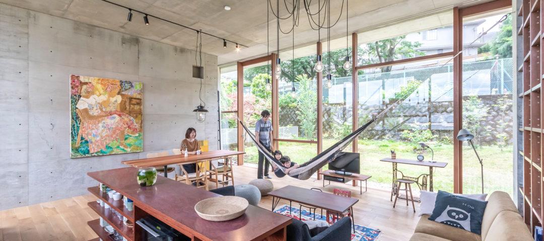 丘の途中に立つ家 開放的で庭の一部のような コンクリート造の空間に住む