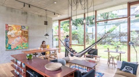 丘の途中に立つ家開放的で庭の一部のようなコンクリート造の空間に住む