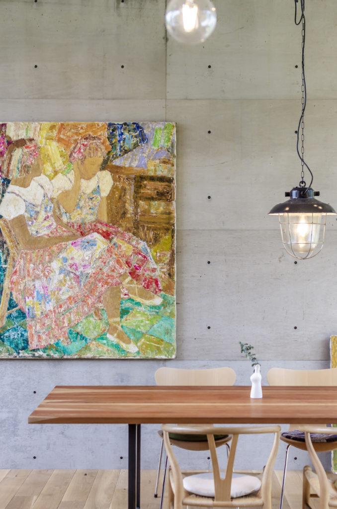 壁に架かる絵はこの敷地の元住人であった画家の遺族から譲り受けたもの。照明器具はアンティーク。
