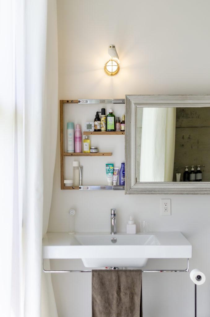 洗面上の額縁に入ったガラスを右にずらすと収納棚が現れる。南側に設けたこの浴室/洗面所では洗濯物も干す。