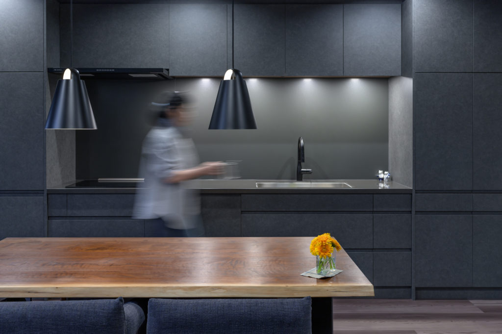 使わない時には家具のように見えるキッチン。キッチンのデザインは、天板をセンターにして、左右対称シンメトリーにした。ダイニングの照明は、ルイスポールセンの「アバーブ」をチョイス。