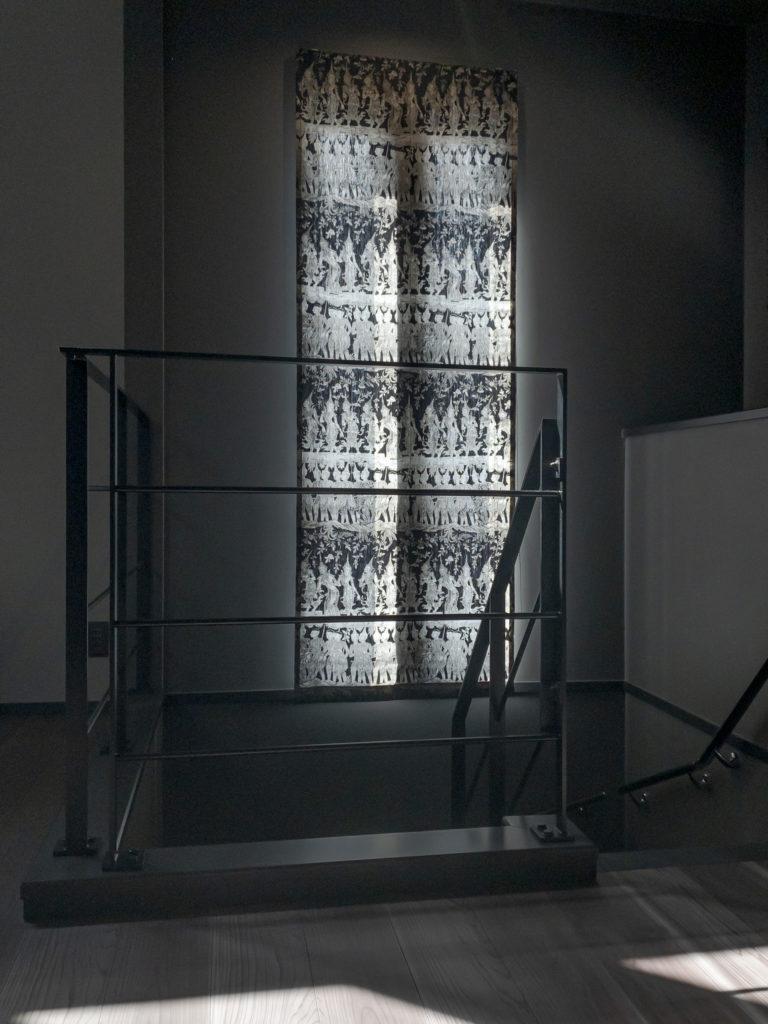 2階へ上がる階段にもアイアンの手すり。北西側にスリット状の明かりとりの窓。 ジムトンプソンのテキスタイルでシェードを。