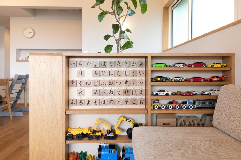 棚の高さは自由に変更可能。左側の50音は、陽くんが最近文字に興味を持ち始めたことで登場。右側に陳列されたラジコンカーは景さんのもの。「子どもたちにはミニカー同様に扱われています」と苦笑い。