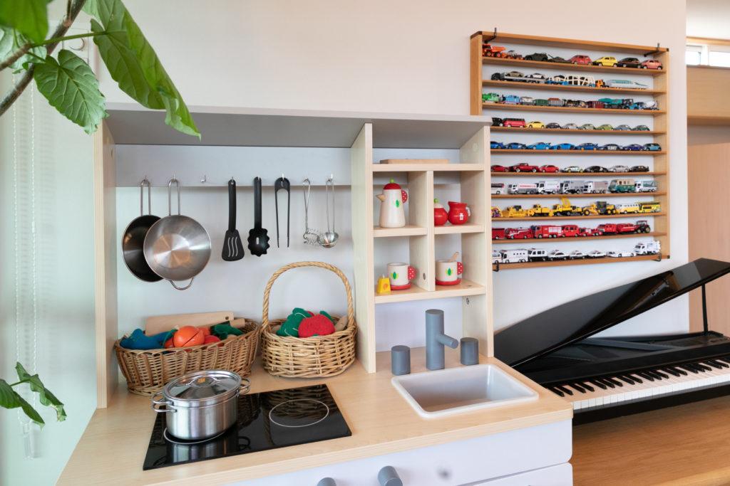 ミニカーが整然と並べられた棚は、雪乃さんのお父様が作製したもの。ミニチュアのグランドピアノは本格的な演奏も可能。ピアノの先生である雪乃さんのお母様からのプレゼント。