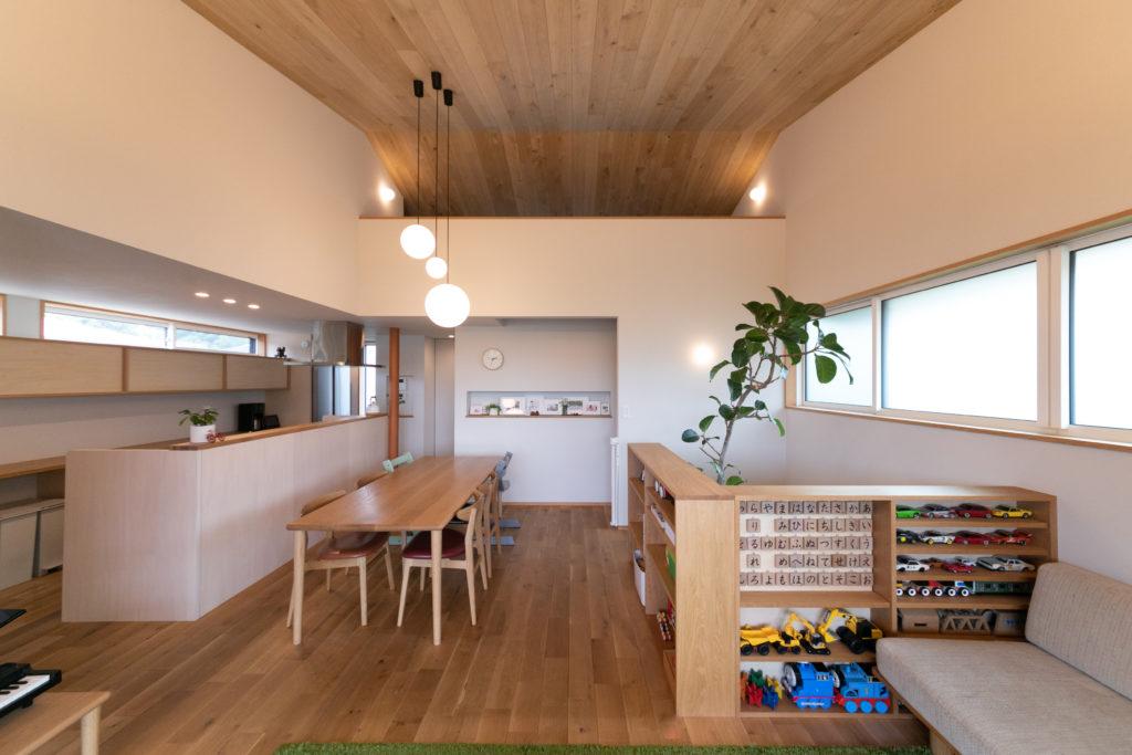 ナラ材を使用した勾配天井が高くて気持ちいい。奥の階段を昇るとロフトへと続く。ダイニング側にシナ材を貼り付けたキッチンは回遊性をもたせ、来客への対応もスムーズに。