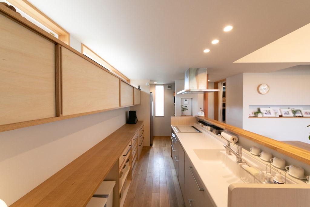 定番サイズのシステムキッチンは、傷みが出てきたらすっぽり入れ替える予定。背面のキッチンカウンターは、床と同じナラ材で統一。