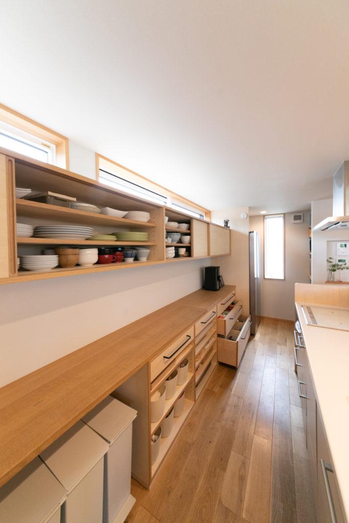 上部の棚には食器類を、下部の引き出しには食品のストック類までたっぷり収納可能。そのためパントリーは造らず、奥のスペースには冷蔵庫と、電子レンジや炊飯器などのゴチャゴチャしがちな家電をまとめた。