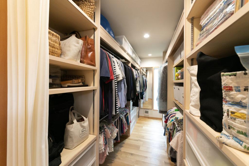 """家族4人分のファミリークローゼット。衣類は、全てハンガー収納に。「友人たちからの""""おさがり""""で、ほとんどいただきものです」という子ども服がズラリと並ぶ。"""